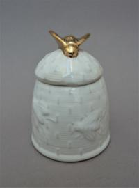 Witte porseleinen honingpot met gouden bij