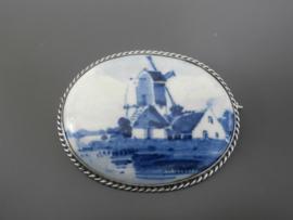 Royale ovale broche met zilveren gedraaide rand.
