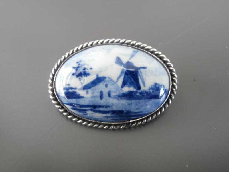 Ovale broche met zilveren gedraaide rand.
