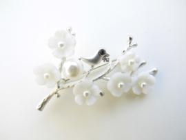 Broche vogeltje op tak met witte bloemen.