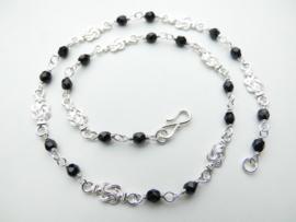 Zilveren baby mattenkloppers zwarte kralen ketting.
