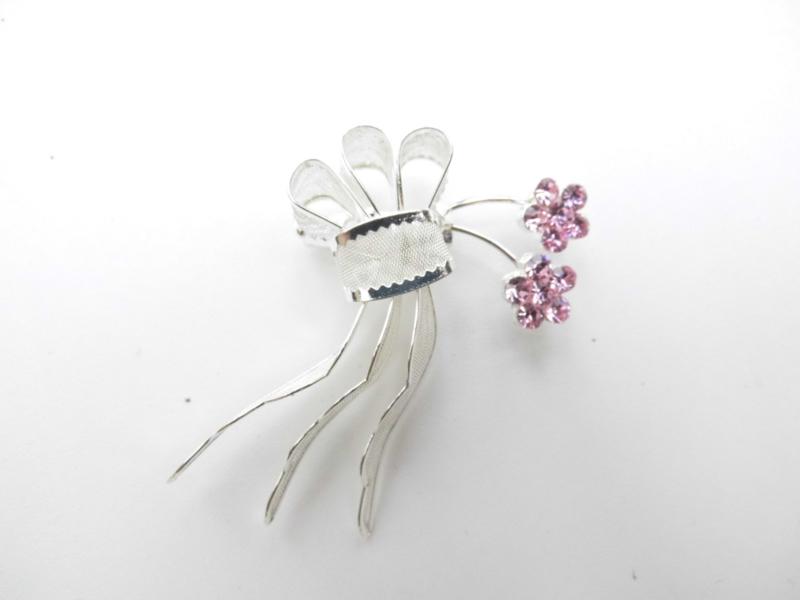 Zilverkleurig filigrain broche met roze steentjes.