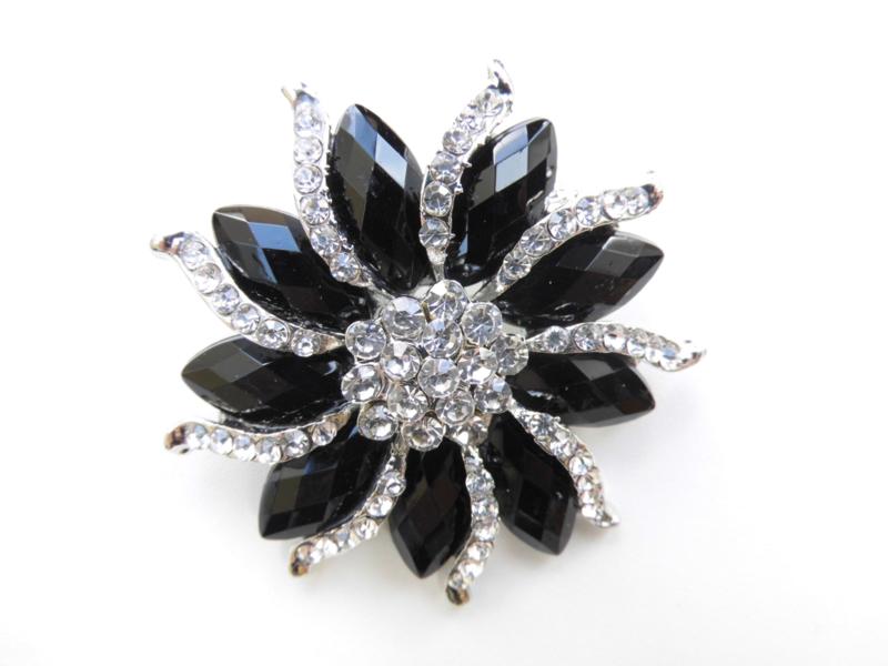 Broche zwart met glitter steentjes.