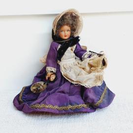 Oud popje met paars gewaad en strohoed