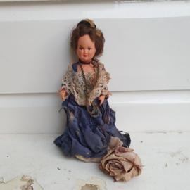 Heel oud popje met versleten blauwe jurk