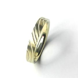 Gouden ring met golvende lijnen op vlakke ondergrond