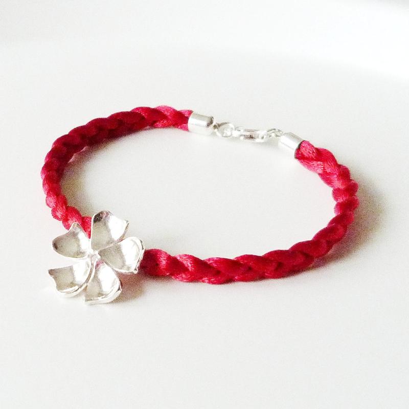 Gevlochten rode satijnen armband met zilveren hanger bloem