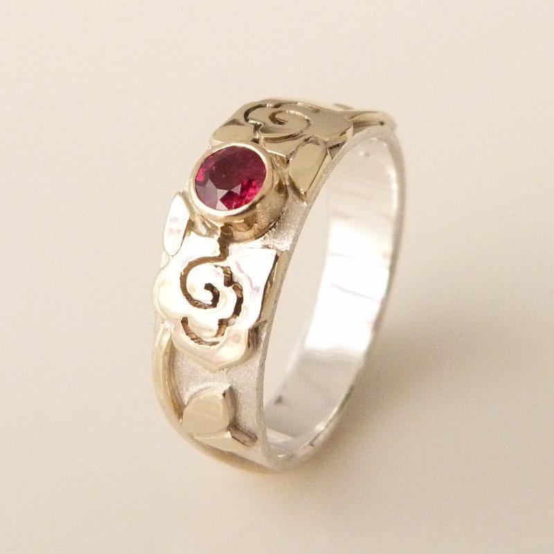 Zilveren ring met geelgouden rozenpatroon en facet geslepen robijn