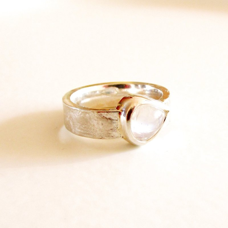 Zilveren ring met kantpatroon en wijde peervormige regenboogmaansteen