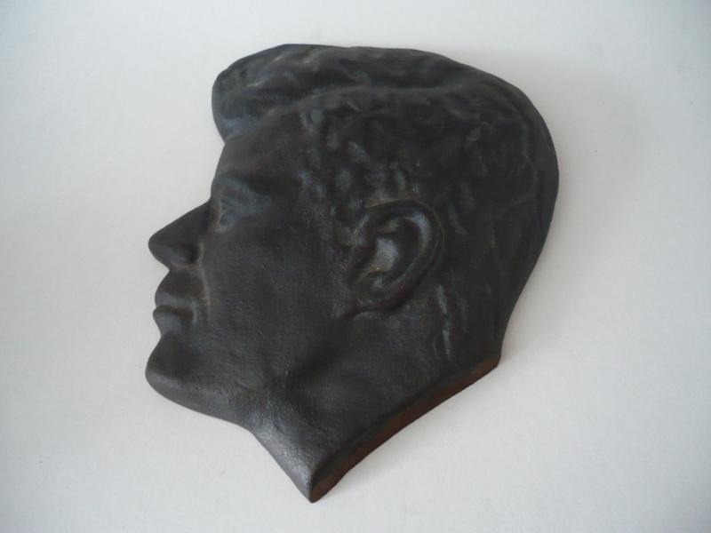 J.F. Kennedy, hoofd, een gietijzeren reliëf