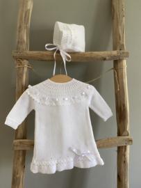 Lief en mooi gebreid jurkje met bijpassende bonnet in het wit.