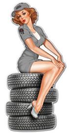 Pin-up Girl zittend op autobanden.  Metalen wandbord 59 x 28 cm.