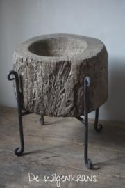 Oude houten vijzelpot op een ijzeren statief