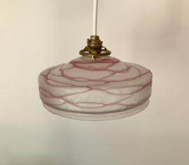 Antieke hanglamp met glazen lampenkap met gedrapeerde roze draden