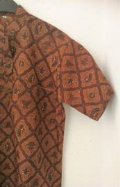 Authentieke Balinese batik blouse met korte mouw en mandarijnen boord. Wordt op de broek gedragen. Met zijsplitjes van 11 cm. Wijdte 114 cm. Lengte 73 cm. Schouderbreedte 49 cm. 100% katoen. Balinese maat L. Ned. maat 54.