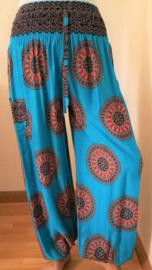 Broek Mandala, blauw/ rood tinten. Met breed elastiek in taille/ heupband, sierkoordje aan voorzijde, opgestikt zijvakje en elastiek in enkels. Binnenbeenlengte 71 cm. Heupwijdte tot 1.20 m, taille tot max 94 cm. 100% rayon. Maat 44/46.