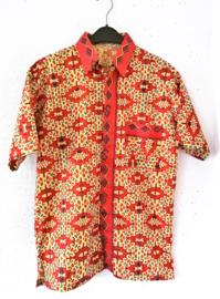 Authentieke Balinese batik blouse met korte mouw en blinde sluiting. Wordt op de broek gedragen. Met zijsplitjes van 11 cm. Wijdte 110 cm. Lengte 73 cm. Schouderbreedte 50 cm. 100% katoen. Balinese maat XL.