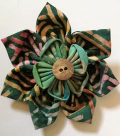 Prachtige bloem corsage/broche van batik stof met kokos knoopje. Diameter 7 cm.