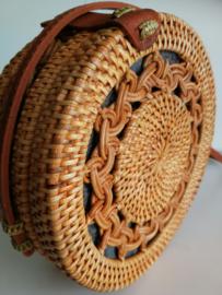 Naturel opengewerkt rotan tasje.  Subliem afgewerkte sluiting en draagband van bruin leer. Lengte band 1.27 cm. Sluit met stevige drukknoop. Diameter 19,5 cm, 7,5 cm diep.