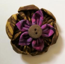 Prachtige bloem corsage/broche van batik stof met kokos knoopje. Diameter 5,5 cm.