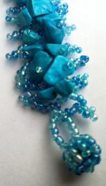 Fluor blauwe armband met ingelegde steentjes. 2,5 x 18 cm