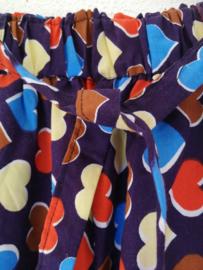 Kinderbroek hartjes paars. Binnenbeenlengte 60 cm. Met elastische heup/taille band en enkels. Met aanstrikband en twee rechte gevoerde  zijzakjes. 100% katoen