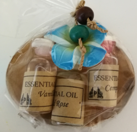 Schaaltje van kokosnoot met drie olietjes van 4,5 ml. Vanilla, Rose en Cempaka (Magnolia).  Voor in een brandertje of verdamper. Kleur bloemetje kan varieren.
