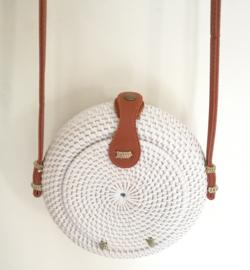 Wit rotan bol tasje.  Subliem afgewerkte sluiting en draagband van bruin leer. Lengte band 1.27 cm. Sluit met stevige drukknoop. Diameter 20 cm, 10 cm diep.