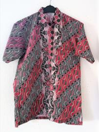 Authentieke Balinese batik blouse met korte mouw en blinde sluiting. Wordt op de broek gedragen. Met zijsplitjes van 11 cm. Wijdte 110 cm. Lengte 73 cm. Schouderbreedte 47 cm. 100% katoen. Balinese maat XXL.