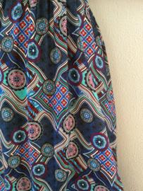 Strapless jurkje 'Picasso'. Gesmockt bovenlijfje, met halterbandje, zijsplitje, lengte 103 cm vanaf bovenkant smockrand. Bovenwijdte rekbaar tot 100 cm. One size voor maat 36 t/m 42. 100% rayon.