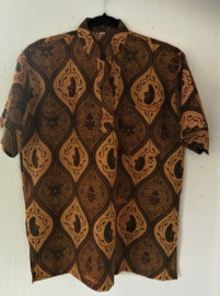 Authentieke Balinese batik blouse met korte mouw en mandarijnen boord. Wordt op de broek gedragen. Met zijsplitjes van 11 cm. Wijdte 118 cm. Lengte 71 cm. Schouderbreedte 49 cm. 100% katoen. Balinese maat XL.