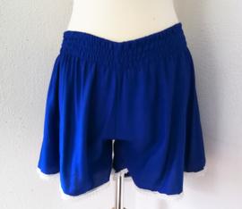 Kort blauw broekje, afgezet met lief kanten randje.  Wijde pijp en elastische taille. Maat 38-40