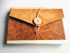 Eenvoudig handgemaakt notitie blokje van rijste papier. Enveloppe model. Sluit met koksnoot knoopje. 15x10 cm. Leverbaar uit assorti.