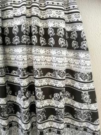 Strapless jurkje '1001 Nacht zwart/wit'. Gesmockt bovenlijfje, met halterbandje, zijsplitje, lengte 101 cm vanaf bovenkant smockrand. Bovenwijdte rekbaar tot 100 cm. One size size voor maat 36 t/m 42.  100% rayon.