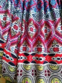 Jumpsuit 'Glas in lood' paars/ blauw multicolour. Strapless gesmockt bovenlijfje, wijd uiteenlopende pijpen, elastiek in de enkels. 100% zacht glanzende rayon. Maat 36 t/m 42.