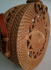 Meesterlijk vlechtwerk dit opengewerkte rotan tasje.  Prachtig afgewerkte sluiting; draagband van bruin leer. Lengte band 1.25 cm. Sluit met sierlus. Diameter 20 cm, 8 cm diep.