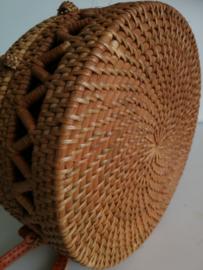 Meesterlijk vlechtwerk dit opengewerkte rotan tasje. Prachtig afgewerkte sluiting; draagband van bruin leer. Lengte band 1.27 cm. Sluit met sierlus. Diameter 20 cm, 8 cm diep.
