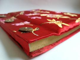 Handgemaakt opschrijfboek signaal rood. Ongebleekt rijstepapier met schitterende velourse stoffen kaft vol libelles, met drie kokosknopen. 20x23x1,5 cm.