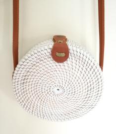 Wit rotan tasje. Subliem afgewerkte sluiting en draagband van bruin leer. Lengte band 1.26 cm. Sluit met stevige drukknoop. Diameter 20 cm 6,5 cm diep.