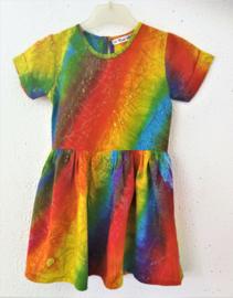 Prachtig handwerk van eigen label. Vrolijk regenboogjurkje. Gemaakt van speciale BingBatik. Mouwtje met omslag en aangerimpelde rok. Sluit met knoopje achter. Maat 98/104 voor 3-4 jaar. 100% rayon, wasbaar op 30  graden.