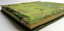 Handgemaakt opschrijfboek mosgroen. Ongebleekt rijstepapier met schitterende velourse stoffen kaft vol libelles, met drie kokosknopen. Handgemaakt 20x23x1,5 cm