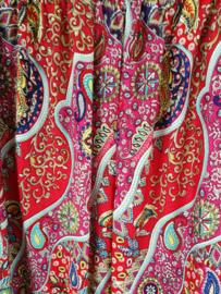 Broek 'Paysley Dream' rood/multi. Met breed elastiek in taille/ heupband, sierkoordje aan voorzijde, opgestikt zijvakje en elastiek in enkels. Ruimvallende pijpen en normale hoogte kruis. 100% rayon. Binnenbeenlengte  76 cm Maat 44 t/m 52.