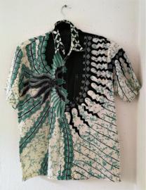 Authentieke Balinese batik blouse met korte mouw en blinde sluiting. Wordt op de broek gedragen. Met zijsplitjes van 11 cm. Wijdte 114 cm (borst/buik). Lengte 70 cm. Schouderbreedte 48 cm. 100% katoen.  Ned. maat 54.