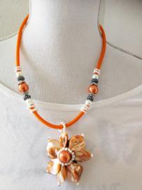 Artistieke ketting in oranje pasteltinten. Gemaakt van rond geslepen parelmoer schelpjes. Nikkelvrije sluiting. Lengte 56 cm.