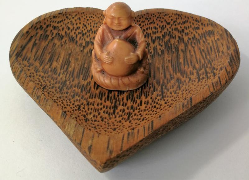 Kleine vriendelijke monnik op Balinees schaaltje van palmhout.