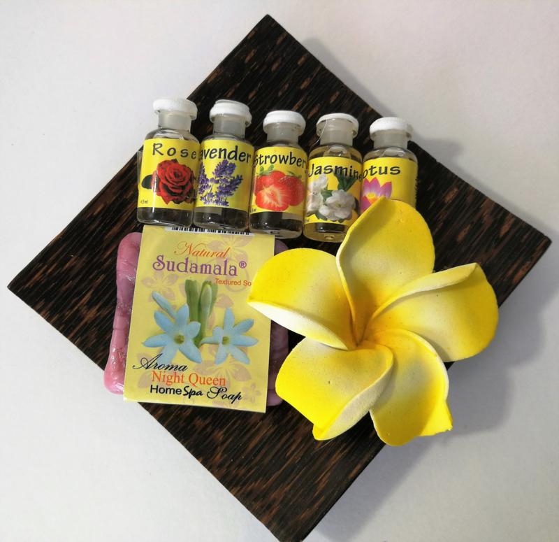 Vierkant schaaltje van palmhout met 5 verschillende olietjes van 4,5 ml. Strawberry, Lavendel, Jasmine, Rose en Lotus. Met Night Queeen home spa seepje en grote frangipani bloem.  Voor gebruik in een brandertje of verdamper.