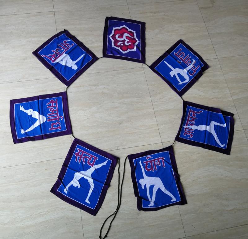 Vlaggenlijn 'Yoga'.  Batik handwerk uit kunstenaarsdorp Ubud. 7 vlaggen van 33x26 cm met 7 afbeeldingen. Lengte inclusief koord  3 meter. 100% rayon