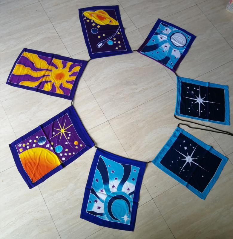 Kosmische vlaggenlijn. Batik handwerk uit kunstenaarsdorp Ubud. Met 7 verschillende kosmische batik afbeeldingen. Afmetingen vlaggen  34x27cm en 44x28 cm. Inclusief koord 3.30 meter. 100% rayon.