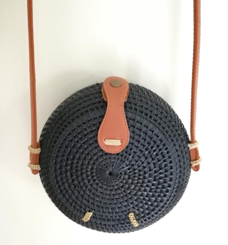 Zwart rotan bol tasje.  Subliem afgewerkte sluiting en draagband van bruin leer. Lengte band 1.23 cm. Sluit met stevige drukknoop. Diameter 20 cm, 10 cm diep.