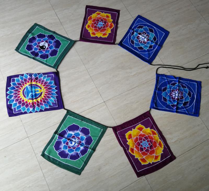 Vlaggenlijn 'Flower of life'.  Batik handwerk uit kunstenaarsdorp Ubud. 7 vlaggen van 33x26 cm met 5 verschillende afbeeldingen. Lengte inclusief koord  2.80 meter. 100% rayon.